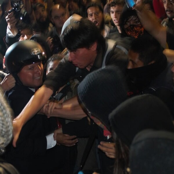 Un policía forcejea con varias personas afuera de Televisa Chapultepec