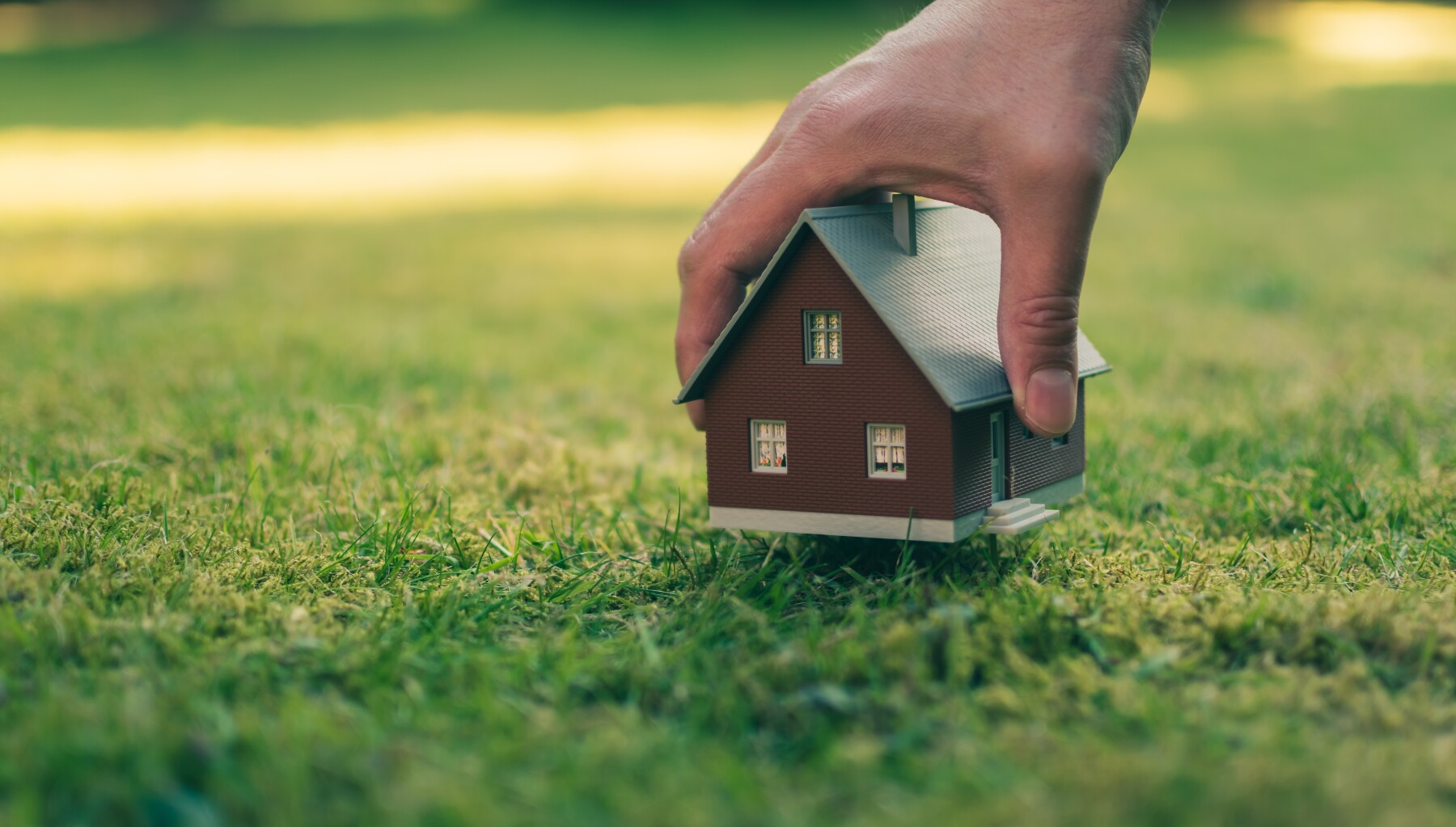 Concept of selling a house. A hand is holding a model house above green meadow.