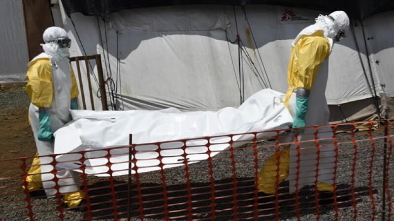 Personal médico traslada a una víctima del ébola en Monrovia, Liberia; el virus mortal continúa cobrando vidas