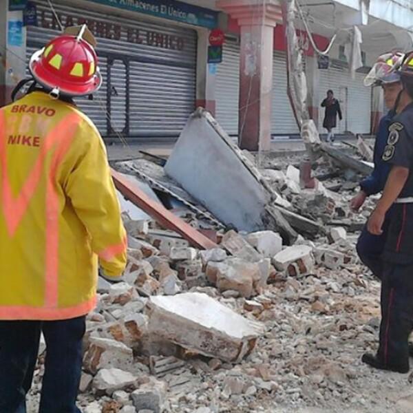 Bomberos de la región de San Marcos, Guatemala, observan un edificio dañado por un sismo de 6.9 grados