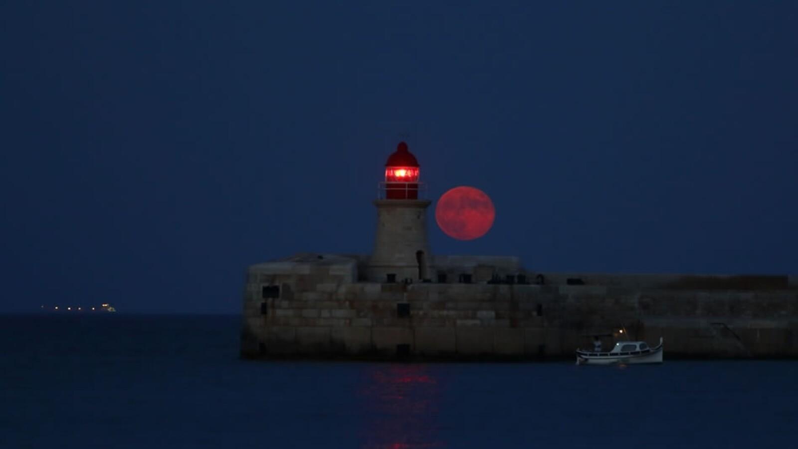 Una luna con tono rojizo aparece en el puerto de La Valeta, capital de Malta