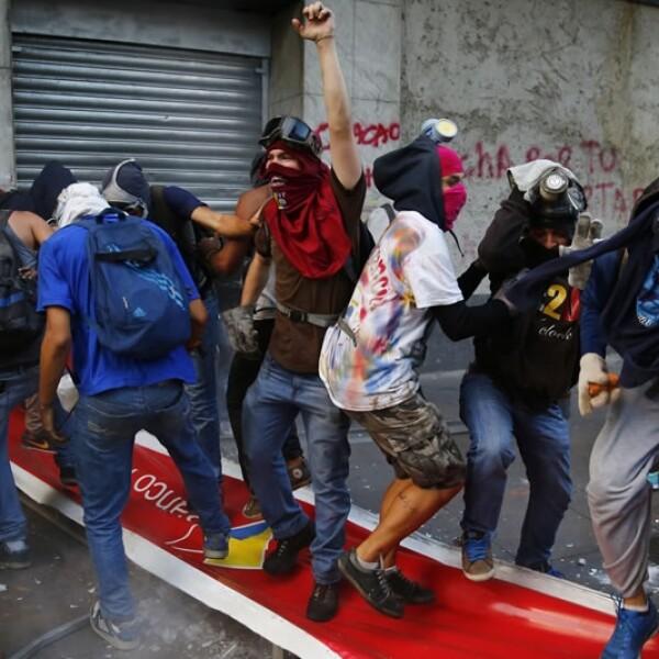 Grupo de manifestantes saltan y pisan un señalamiento del Banco de Venezuela durante los enfrentamientos en la capital venezolana