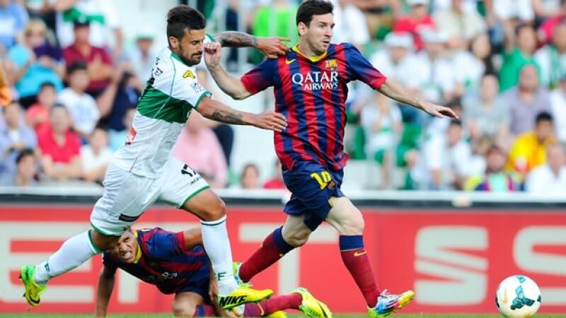 Lionel Messi de Barcelona compite por el balón con Javi Márquez de Elche; el argentino no pudo marcar para acercar a su equipo al título de la LIga