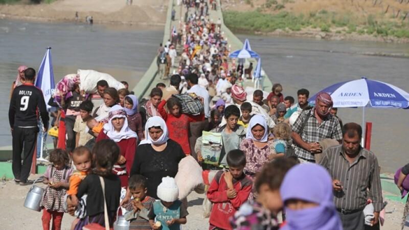 Iraquíes desplazados de la comunidad yazidí cruzan la frontera de Siria con Iraq, acechados por el grupo extremista ISIS