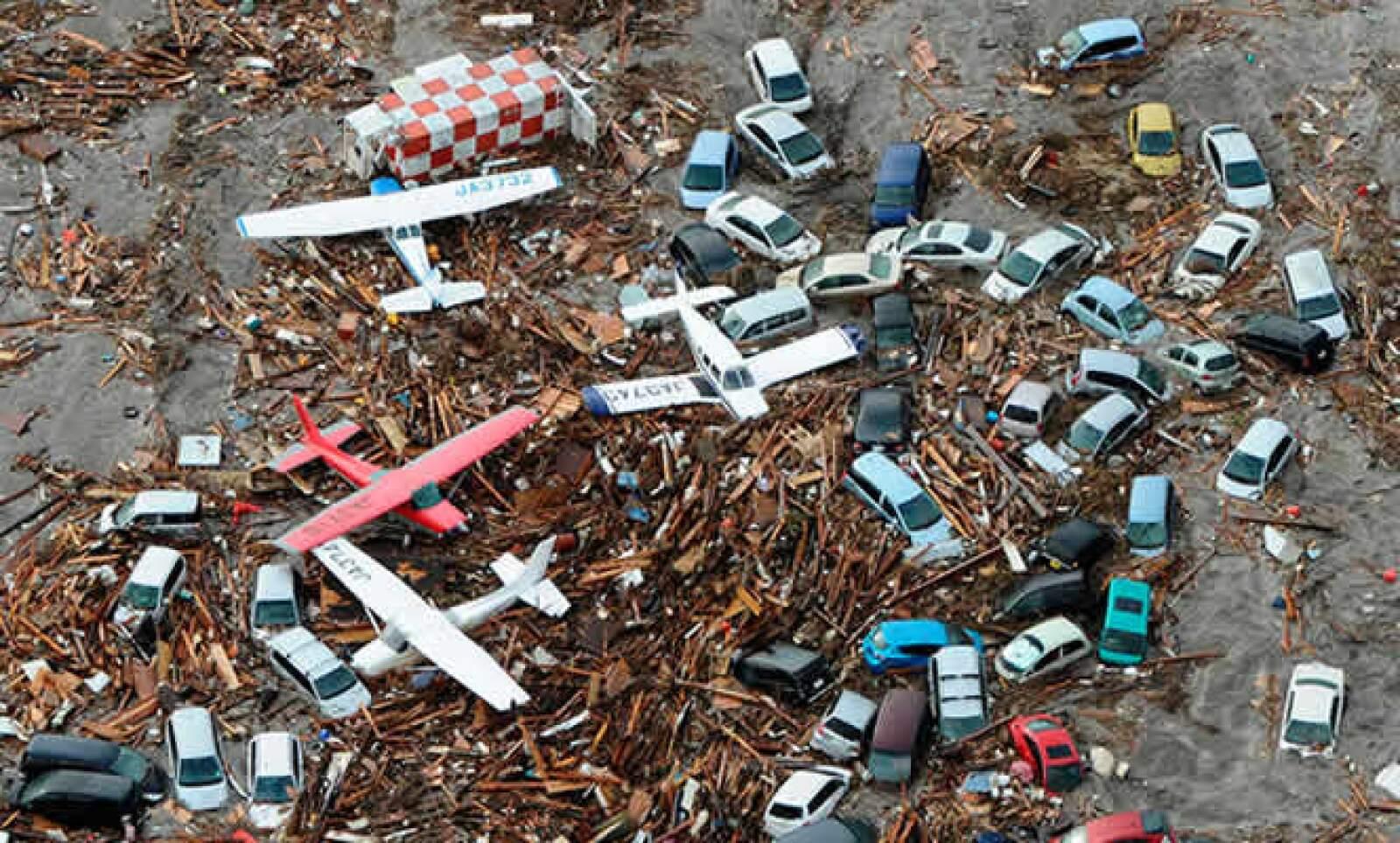 Casas y aviones son llevados por la corriente del tsunami, a pocos kilómetros del aeropuerto de Sendai, al noreste de Japón.