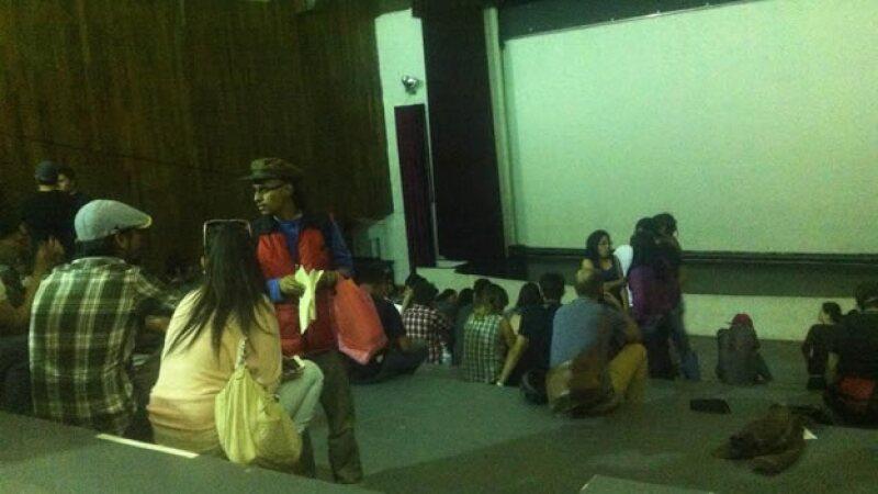 Un grupo de personas dentro del auditorio de la UNAM Ernesto 'Che' Guevara, tomado por varios individuos