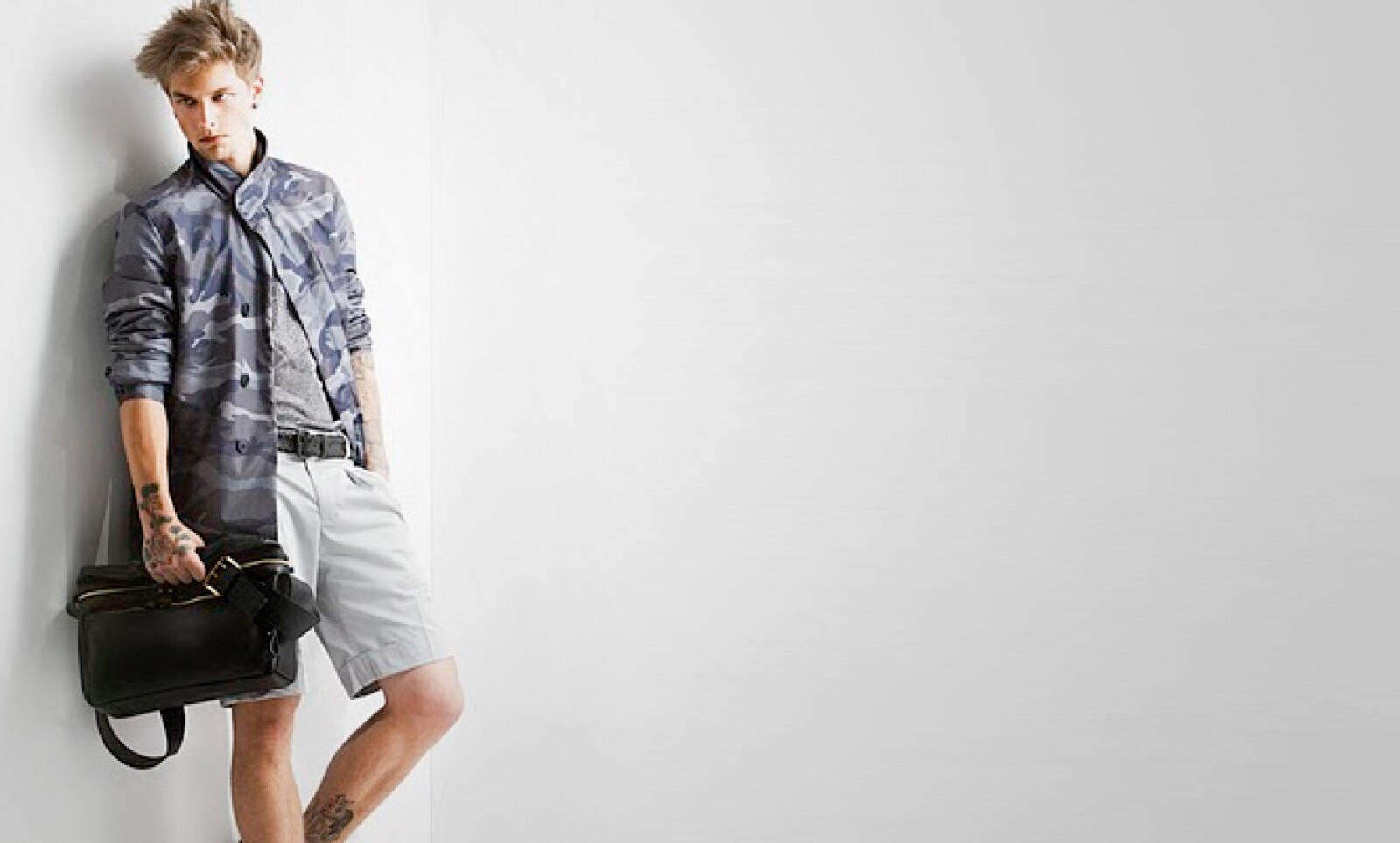Un 'look' más atrevido con este 'blazer' con camuflaje, pantalones cortos y un maletín de piel.