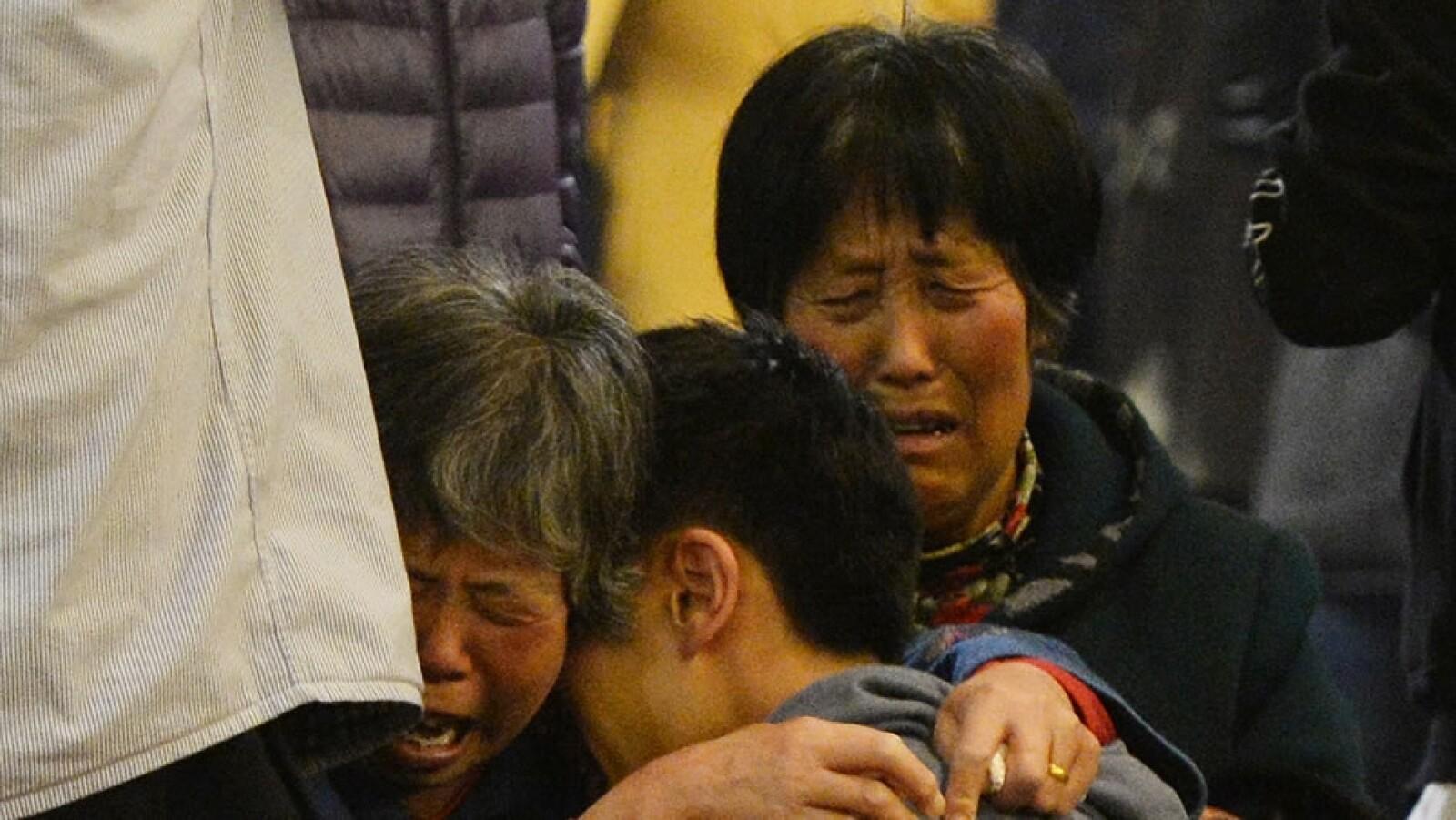 Una mujer abraza a su pariente mientras se entera de las noticias del avión desaparecido