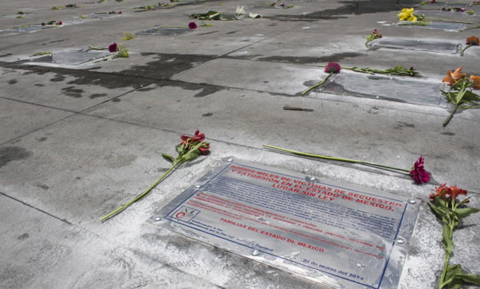 Los asistentes colocaron flores en las placas colocadas en La Estela de Luz, en conmemoración por las víctimas de la violencia en algunas regiones del país.