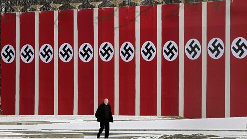 un hombre pasa ante banderolas con la cruz gamada en berlin