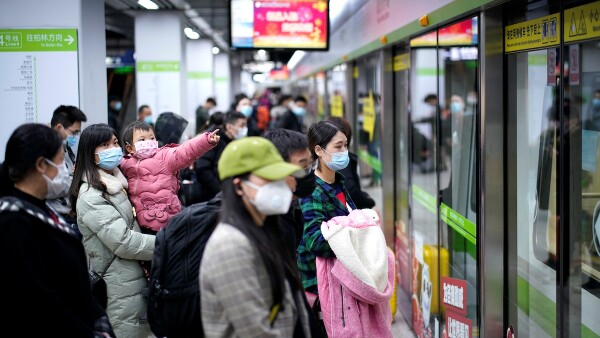 People wearing face masks wait for a subway train on the first day the city's subway services resumed following the novel coronavirus disease (COVID-19) outbreak in Wuhan