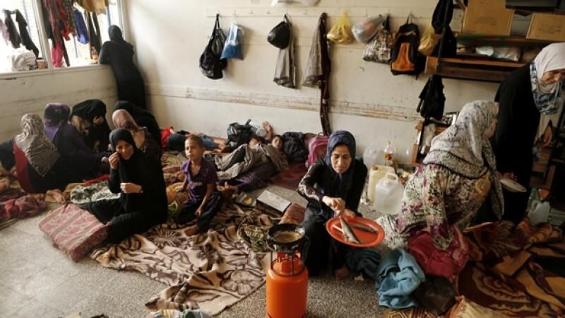 Una mujer palestina desplazada cocina en un salón de una escuela de Naciones Unidas en Jabalia, al norte de la frontera de Gaza