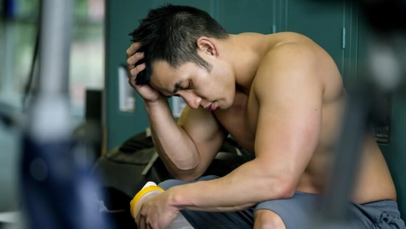 un hombre luce exhausto tras hacer ejercicio en el gimnasio