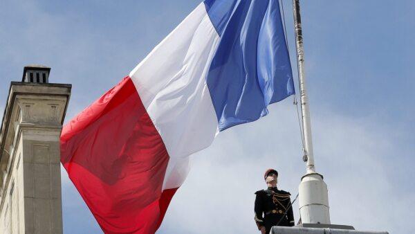 Un soldado de la Guardia Republicana de Francia iza a media asta la bandera francesa.