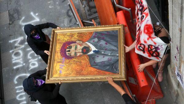 Colectivas de feministas cargaron uno de los cuadros intervenidos durante el tercer día de la toma de las instalaciones