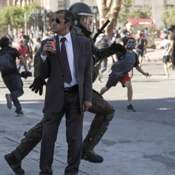 A man drinks a Frucola as a policeman chases demonstrators during a protest against Chile's government in Santiago