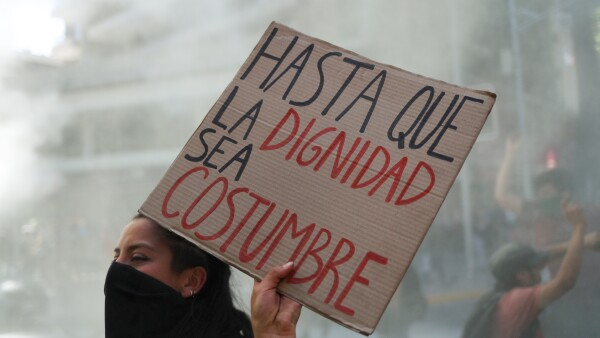 "A demonstrator holds a placard reading ""Until dignity becomes custom"" during a protest at Providencia, a wealthy neighborhood, in Santiago"