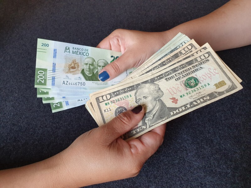 women hands exchanging Mexican banknotes and American dollar money