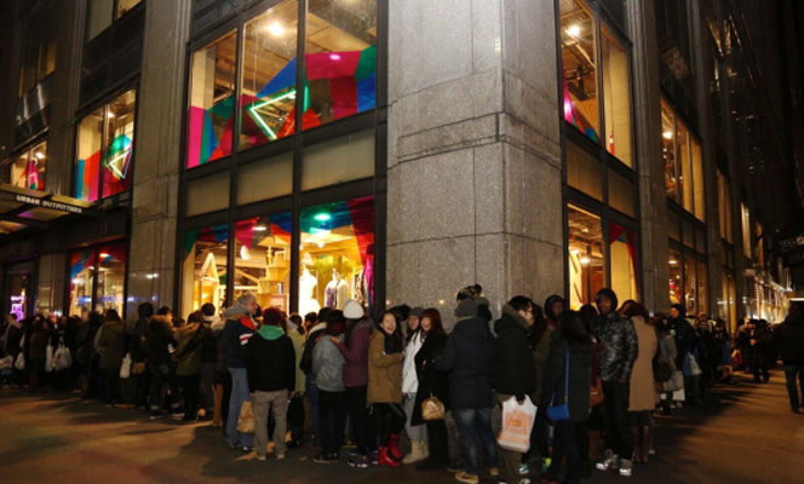 En Nueva York, una fila de asistentes esperan que se abran las puertas luego del 70% de descuento anunciado en la tienda.