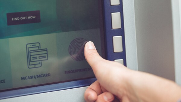Woman at ATM using fingerprint recognition technology