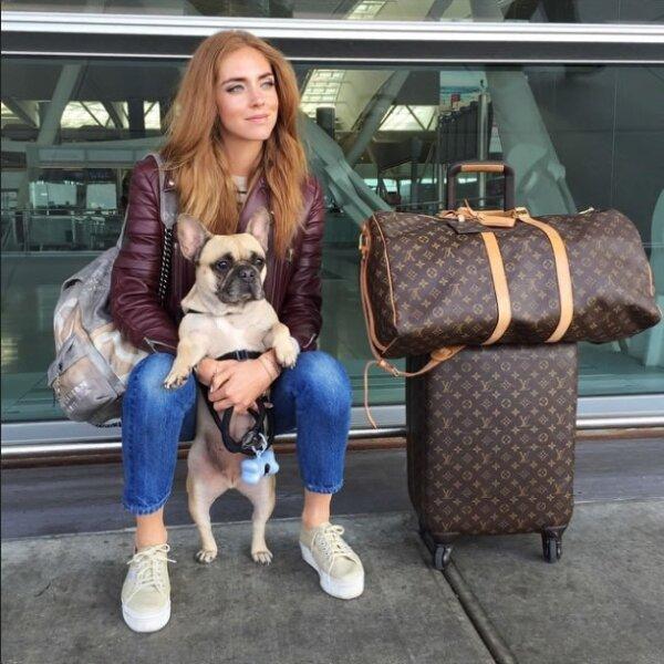 En jeans y chamarra de piel, Chiara regresa a Los Ángeles con su perrita Matilda. Sus maletas Louis Vuitton no pueden faltar.