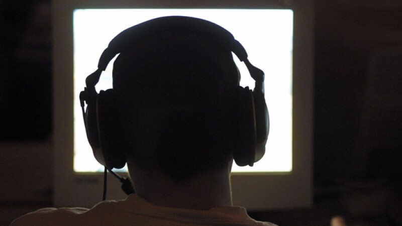 un hombre con audifonos frente a una pantalla