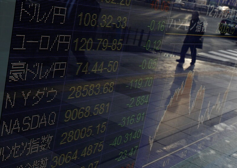 A man is reflected in an electronic display showing world markets indices and exchange rates of the Japanese yen against world currencies outside a brokerage in Tokyo