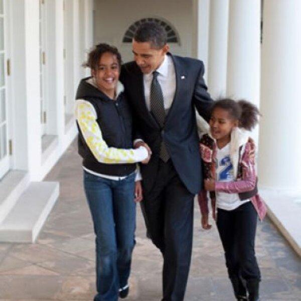 Barack y sus hijas, Malia y Sasha, caminando por la Colonnade.