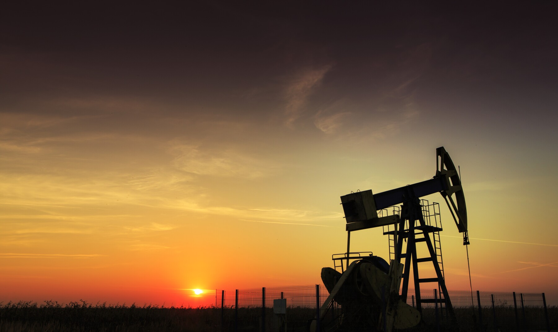 An oil and gas well operating during sunset