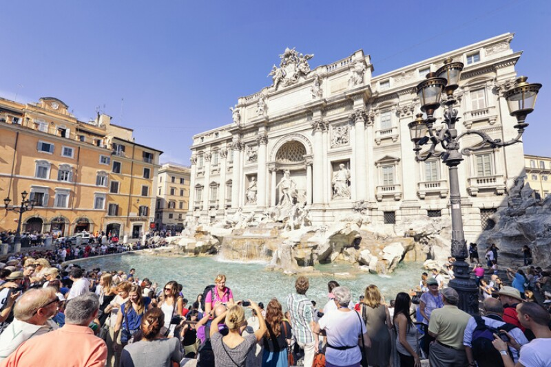 Tourists surrounding the Trevi Fountain in Rome