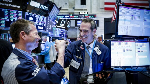 Traders celebrate as they work on the floor at the NYSE in New York