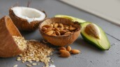 Healthy food concept with avocado, cocos, almonds and oatmeal over gray background near window.