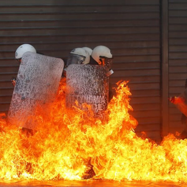 Un grupo de personal de seguridad quedó envuelto en llamas después de que manifestantes arrojaron bombas de gasolina.