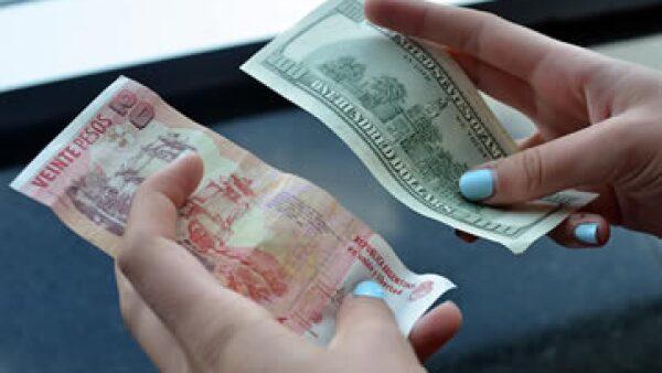 Unos 20 pesos argentinos y 100 dólares son sostenidos por una persona en un casa de cambio de Argentina (Foto: Getty Images)