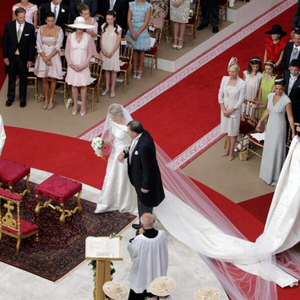 Charlene optó por la sencillez. No porta joyas y tampoco tiara. La cola del vestido es muy larga y el velo también es sencillo. Podemos decir que Charlene es una novia clásica. Camina de la mano de Michael, su padre.