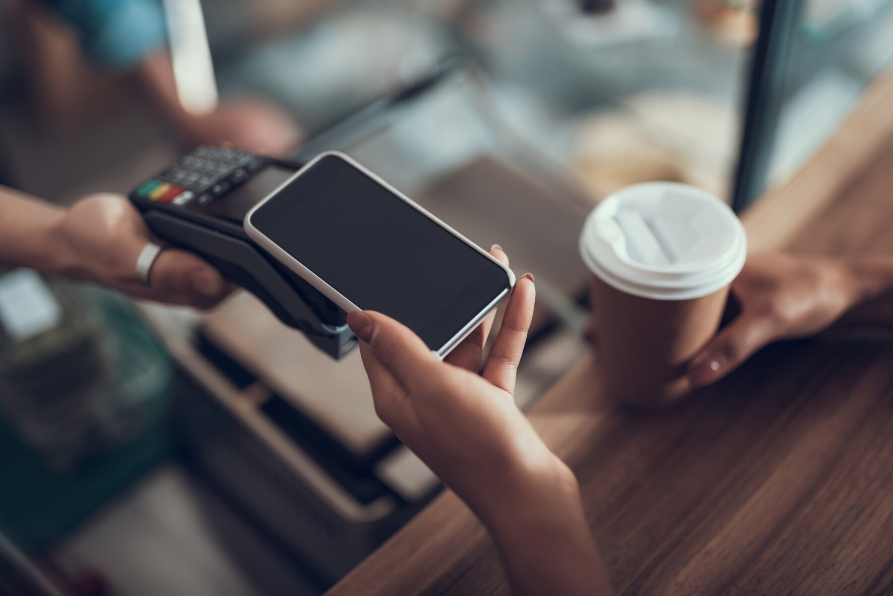 Hand of young lady placing smartphone on credit card payment machine