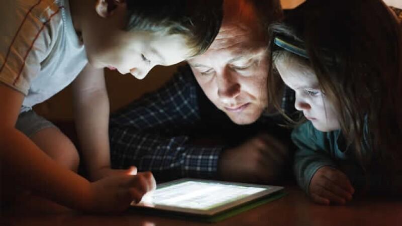 un padre juega en una tableta con sus hijos