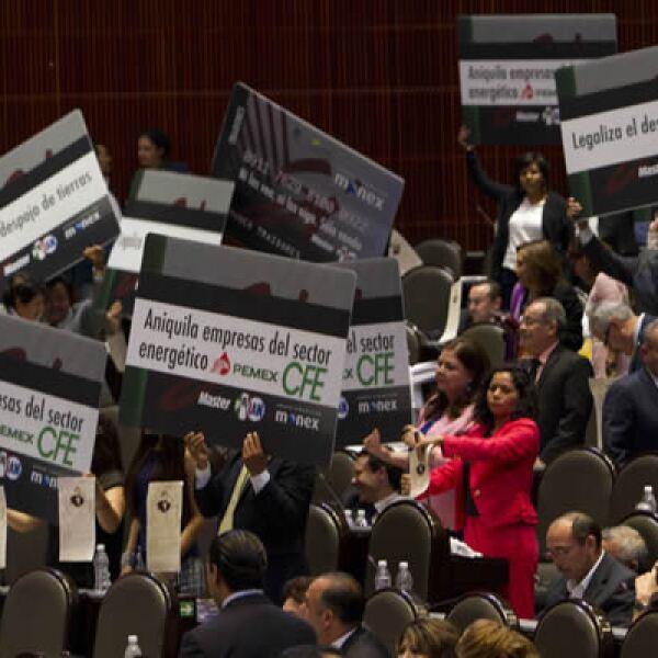 Desde sus curules los diputados mostraban carteles en forma de monederos electrónicos en los que escribieron consignas que acusan que la nueva legislación es un despojo.