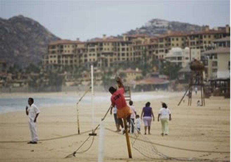 A pesar de la alerta, algunos turistas se resisten a dejar la playa, e incluso surfistas buscan aprovechar las grandes olas. (Foto: AP)