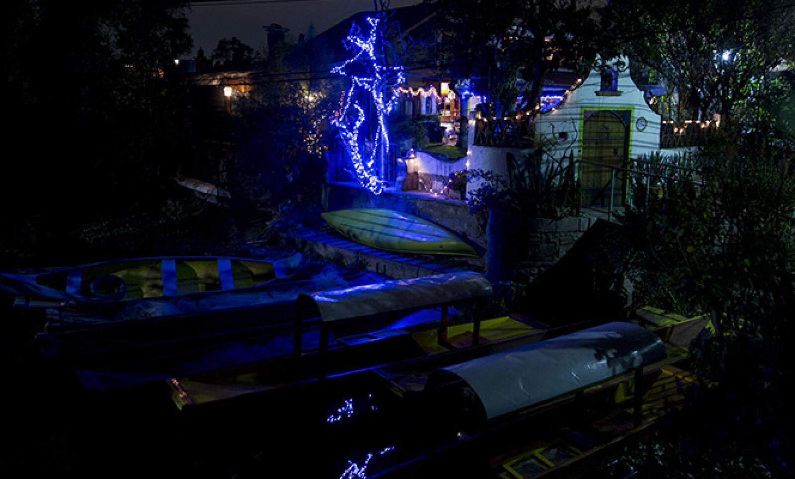 Las luces alumbran a algunas trajineras en las orillas del Lago de Xochimilco.