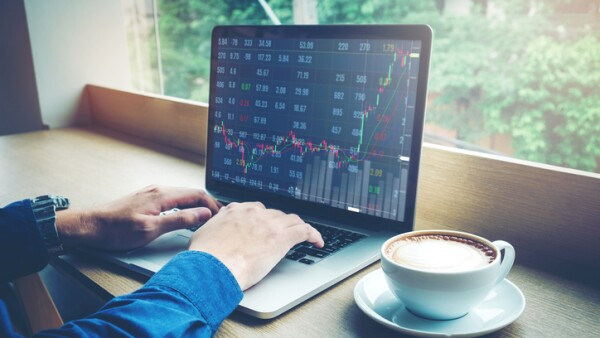 Business man working Laptop Stock market exchange information and Trading graph