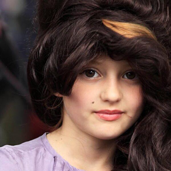 Mila Chetta-Sechi, de ocho años de edad y vestida como la cantante, mira cómo la gente deja flores y recuerdos afuera de la casa en donde vivía Amy.
