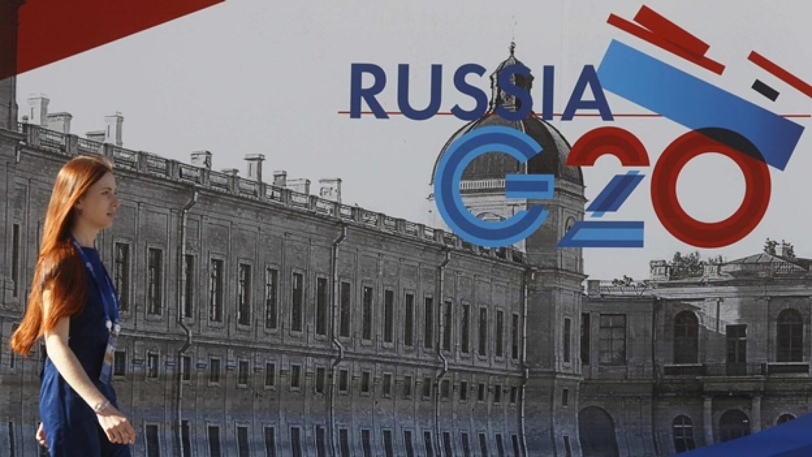 una empleada pasa junto a un letrero dle g-20