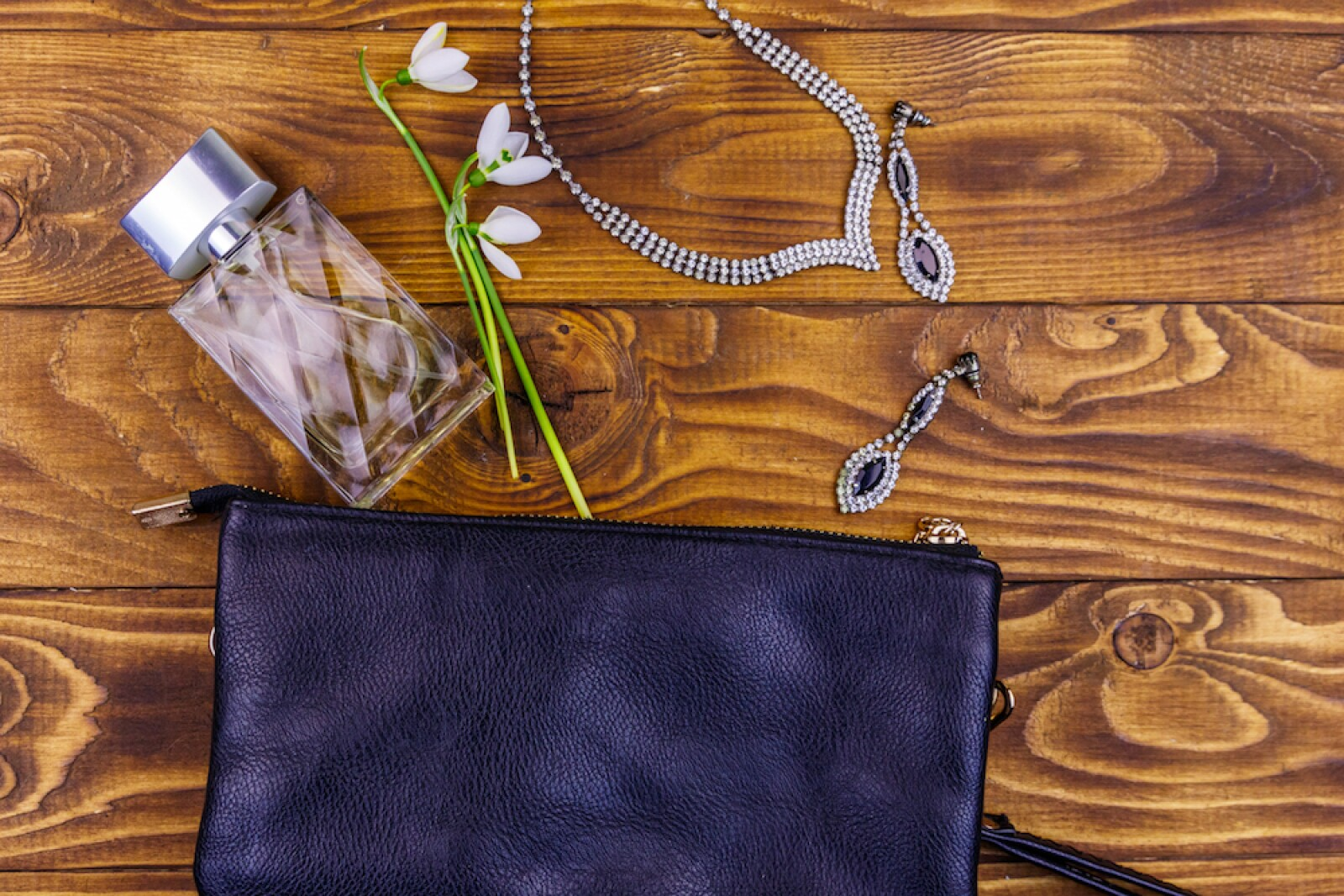 Women accessories on wooden background. Clutch bag, bottle of perfume, necklace, earrings and snowdrops on wood table. Beauty and fashion composition. Top view, flat lay