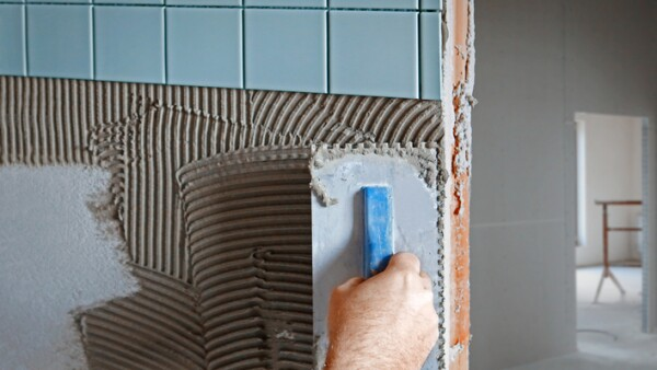 Tiler making new facing on the wall