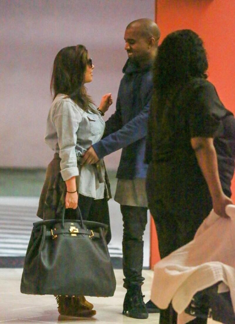 Kanye acomodó la sudadera de su pareja mientras le sonreía.