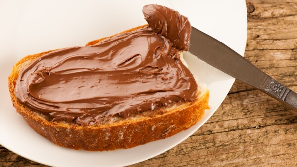 Slice of bread with sweet chocolate nougat spread white plate