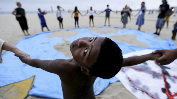 A child and climate change activists attend the Extinction Rebellion protests on Copacabana beach in Rio de Janeiro