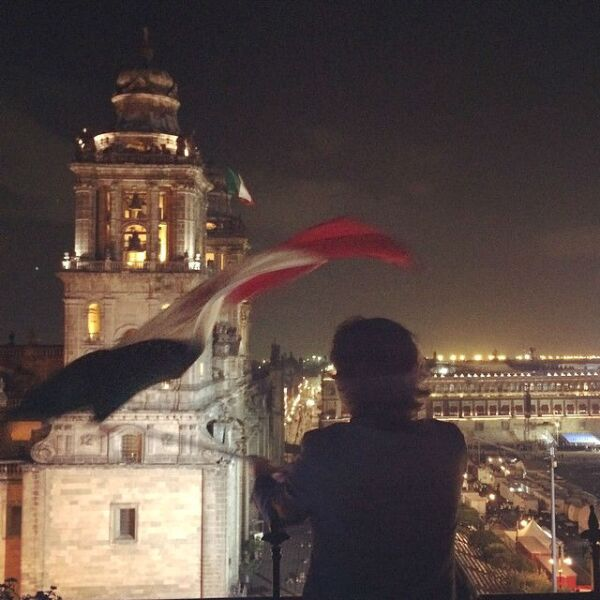 Alan Estrada ondeando la bandera mexicana desde la terraza de un hotel a un costado del Zócalo.