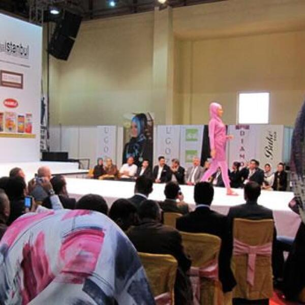 Hombres y mujeres con pañuelos en la cabeza observan el desfile de moda islámica